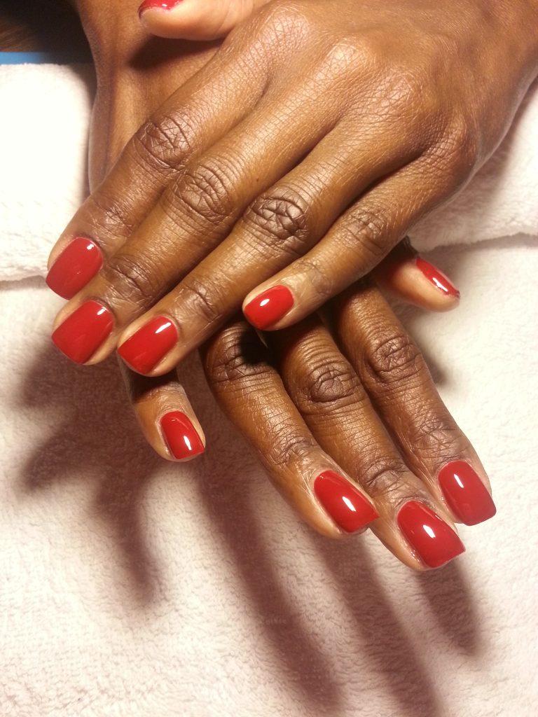 赤色のマニキュアを塗った爪
